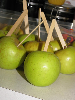 green apples with Popsicle sticks ready to be dipped into caramel