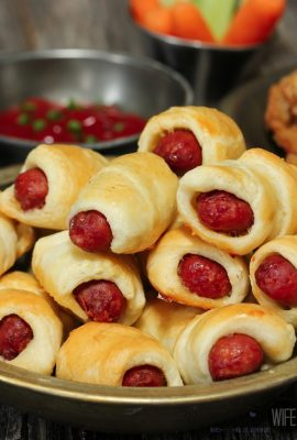 PIGS IN A BLANKET stacked on plate with dipping sauce