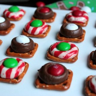 These Chocolate Kiss Pretzel Bites are little pretzel squares that are topped with chocolate kisses, melted in the oven and then topped with sweet chocolate candies! They're the perfect sweet and salty dessert!