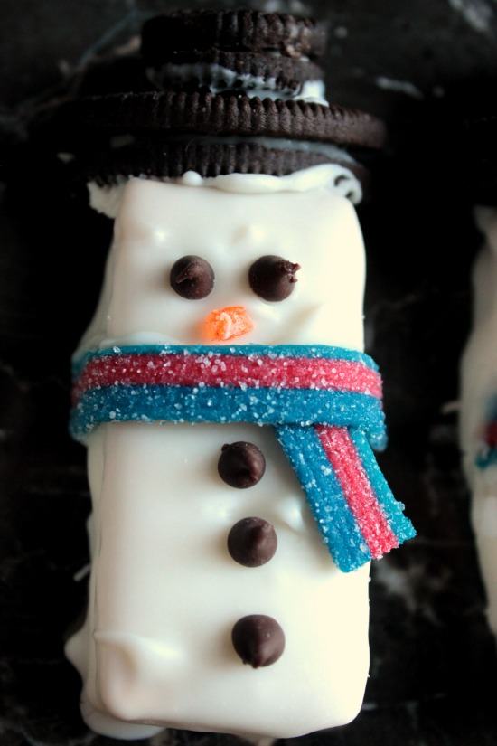 CHOCOLATE COVERED SNOWMAN S'MORE SANDWICHES  Graham Crackers, Marshmallow, Chocolate and Candies make up these Chocolate Covered Snowman S'more Sandwiches! Top them with Oreo hats and candy scarfs and serve them at your Holiday Party!