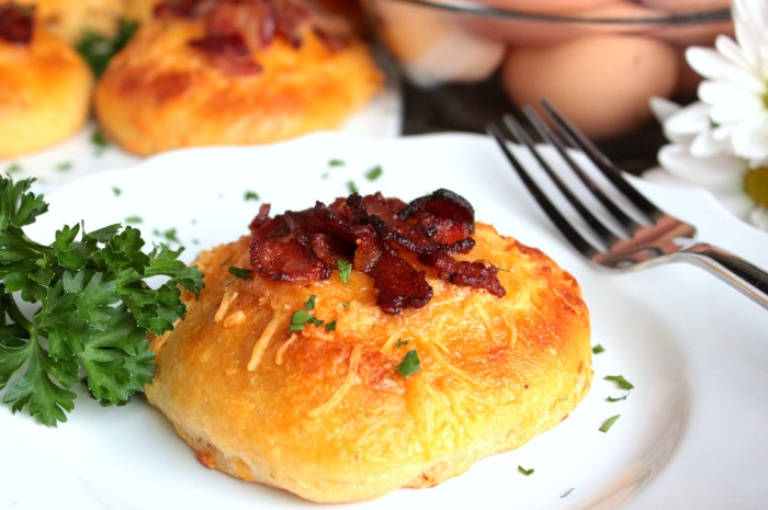 side view of Bacon and Egg Stuffed Biscuit on white plate with parsley and a fork