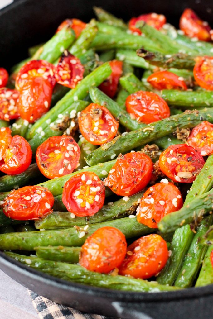 A skillet of Roasted Garlic Sesame Seed Green Beans and Tomatoes