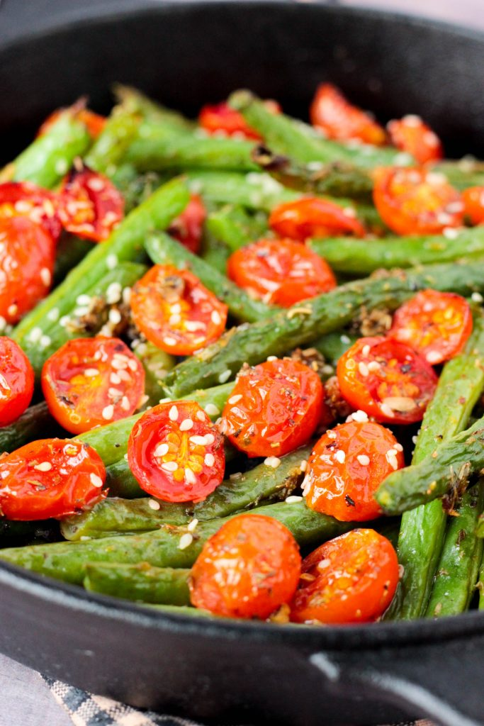 close up of Roasted Garlic Sesame Seed Green Beans and Tomatoes in a cast iron skillet
