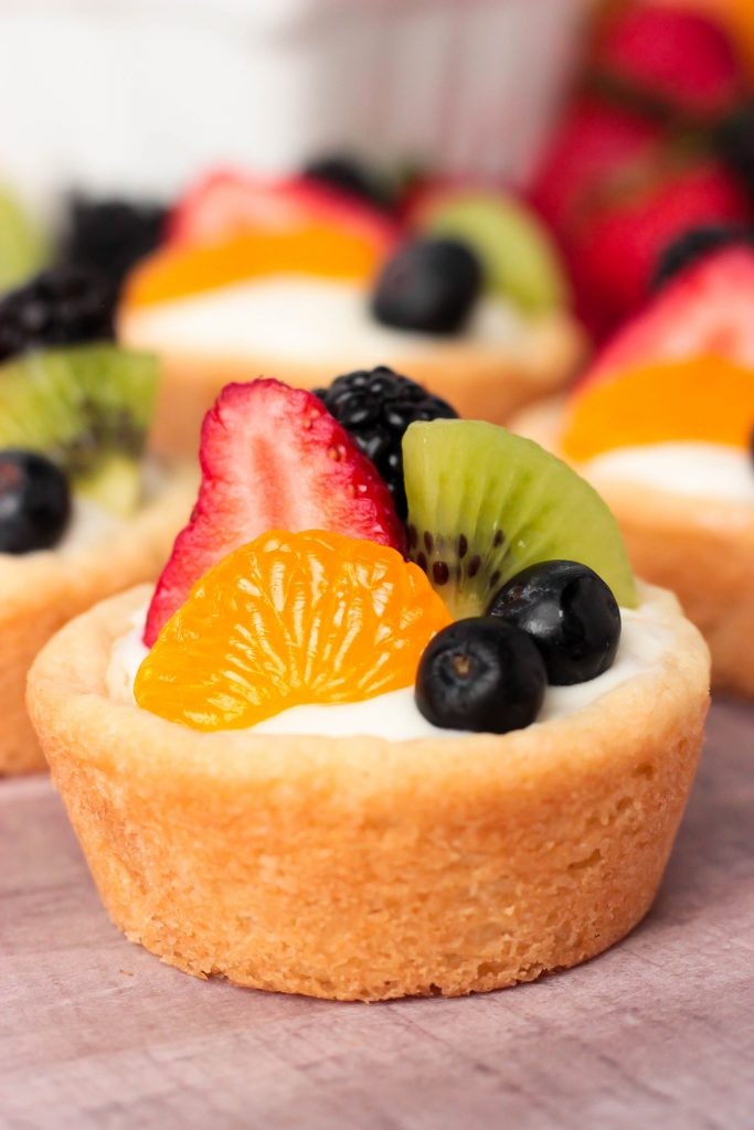 Summer Fruit Sugar Cookie Cups - Homemade sugar cookie cookie cups filled with a cream cheese filling and topped with fresh summer fruit. These Summer Fruit Sugar Cookie Cups are perfect for cookouts and weekend picnics. This dessert is like a fruit pizza stuffed into a sugar cookie cup!