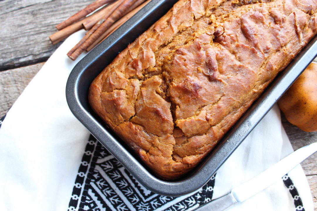 A gray, standard sized loaf pan with baked Easy Pumpkin Bread inside. A white and black tasseled Aztec print towel is under the loaf pan and a pile of cinnamon sticks is resting to the upper right of the pan. An orange, artificial pumpkin is to the upper left of the pan and everything is on a wooden board back drop.