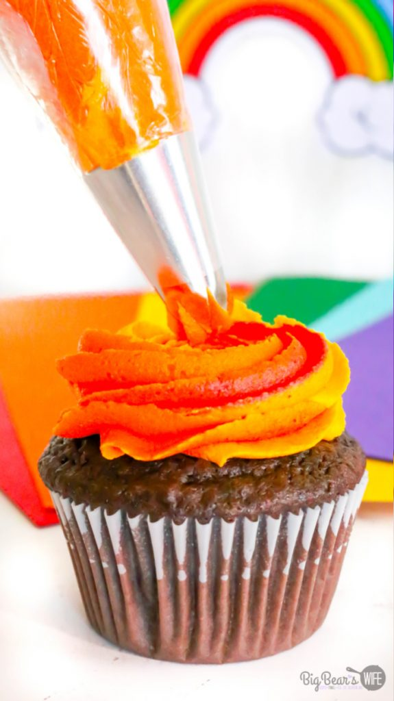 Swirling Red yellow and orange swirl icing onto Homemade Mickey Mouse Rainbow Cupcakes