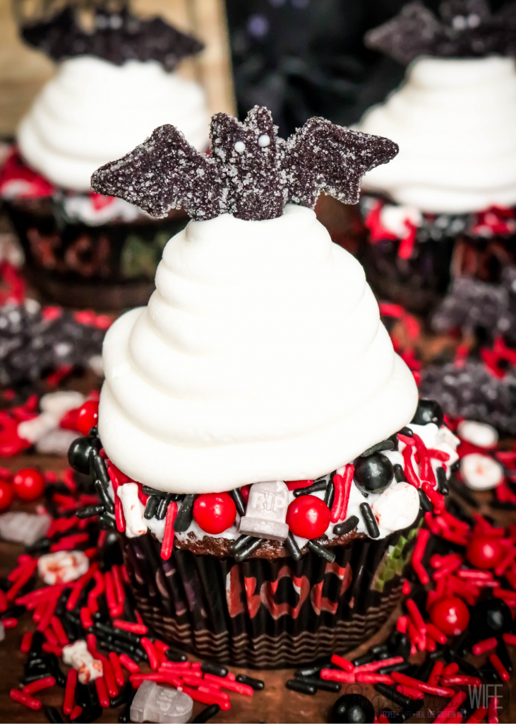 Vampire Bat Cupcakes - Welcome Halloween with these fun and easy Vampire Bat Cupcakes! Vampire bats are resting on top of each cupcake  but they made sure to snag a bite before they did!