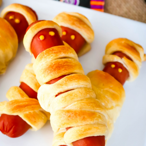 This CrescentRoll Mummy Dogs treat is a super easy savory Halloween treat! You'll need hot dogs and crescent rolls plus whatever you want to use as mummy hot dog eyes!