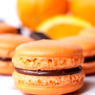 Dive into a sweet combination of orange and chocolate with these fantastically festive Orange Chocolate Macarons. These macarons have an orange flavored shell and they are filled with a wonderful homemade chocolate ganache.