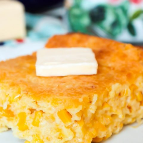 Slice of Creamed Corn Cornbread _ Creamed Corn Casserole with a pat of butter on a white plate (1)