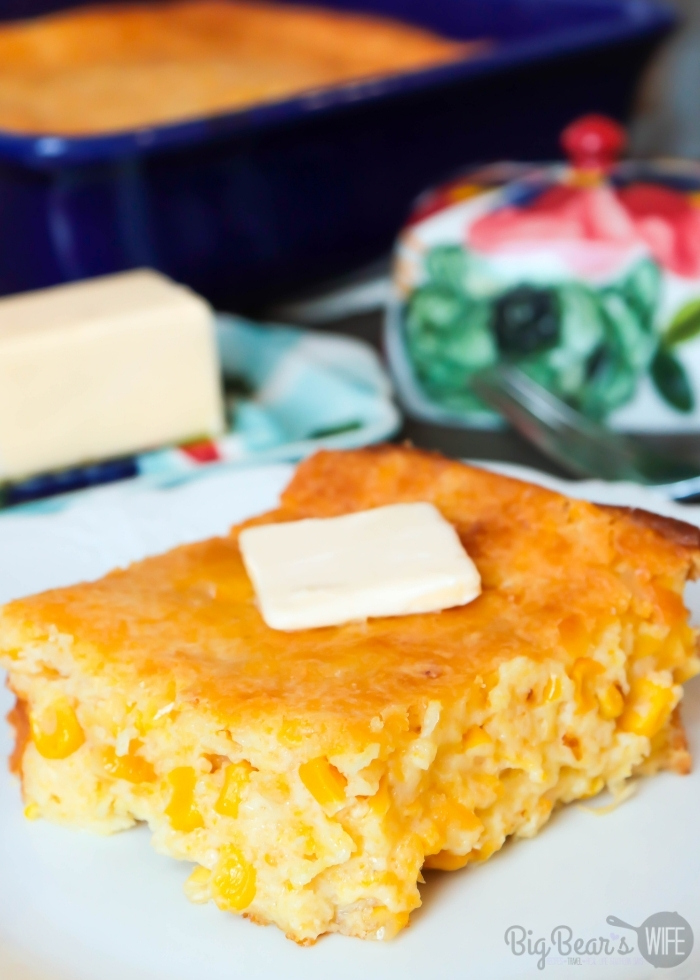 Slice of Creamed Corn Cornbread _ Creamed Corn Casserole with a pat of butter on a white plate