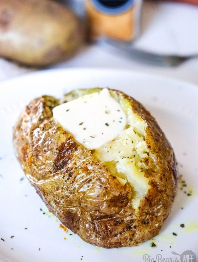 Baked Potato Cut open on white plate with butter and parsley