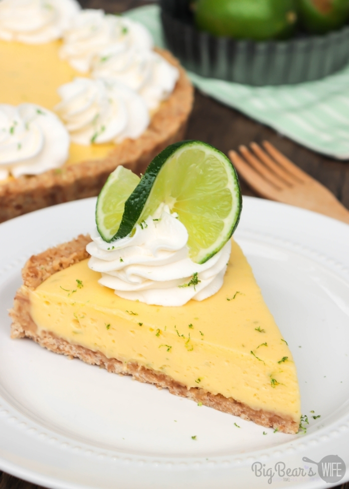 Slice of KEY LIME TART with whipped cream topping and lime zest on white plate (1)