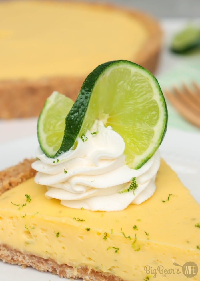 _twisted lime slice on whipped cream topping on a slice of key lime tart on white plate