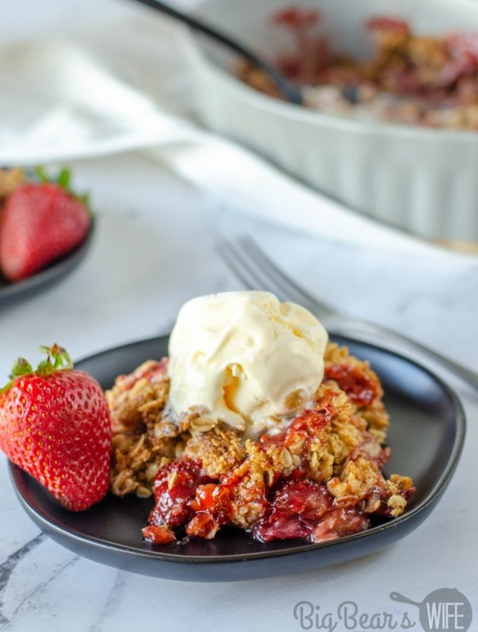 Homemade Strawberry Cobbler with a scoop of vanilla ice cream on black plate