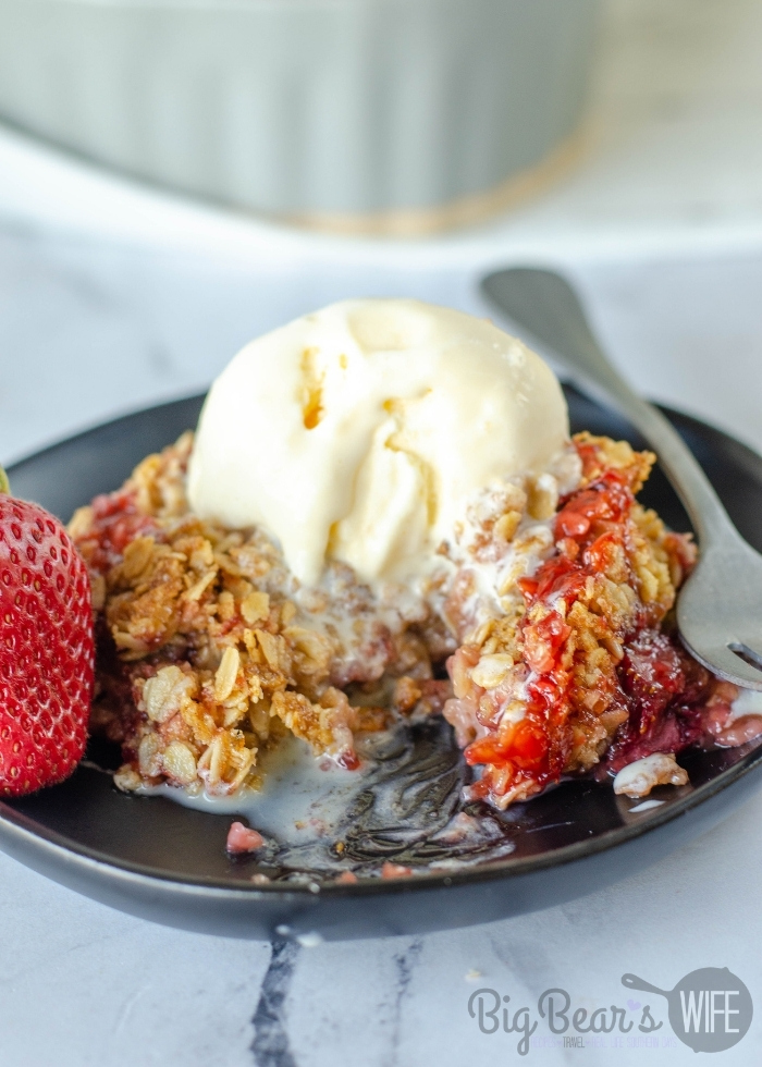 Homemade Strawberry Cobbler with a scoop of vanilla ice cream missing a bite on black plate