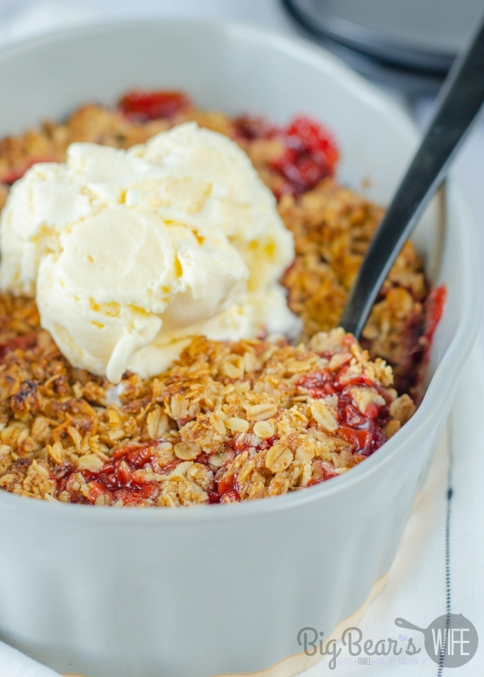 Homemade Strawberry Cobbler with a scoop of vanilla ice cream in baking dish