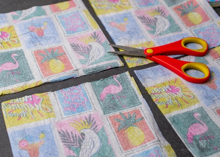 Use scissors to cut one napkin with design layer into 4 squares