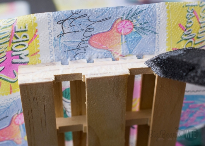 """Add Mod Podge to the """"left and right flat sides"""" of the pallet and fold the napkin down, pressing gently and evenly."""