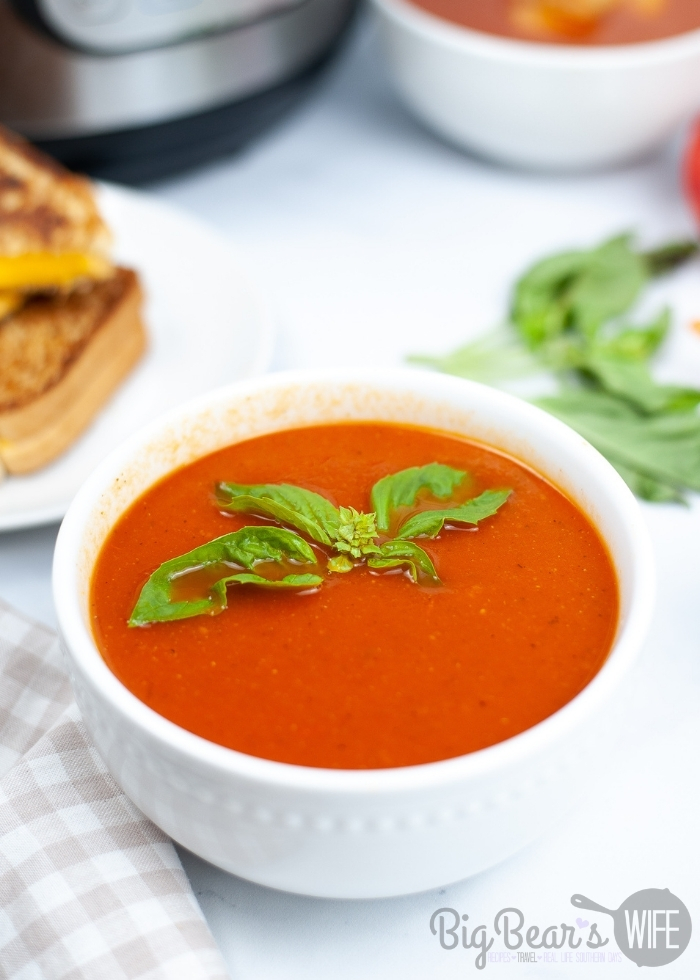 INSTANT POT TOMATO SOUP in white bowl with grilled cheese in back ground