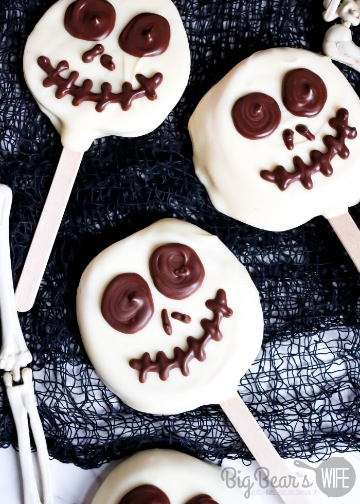 Jack Skellington Apple Slices - Apple slices stuck on a popsicle stick and then dipped in white chocolate candy coating before getting a fun chocolate Jack Skellington face pipped on!